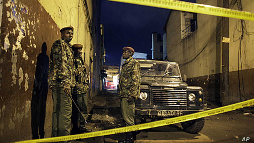 Kenyan police guard the scene of a suspected grenade blast at a pub in downtown Nairobi, Kenya, October 24, 2011.