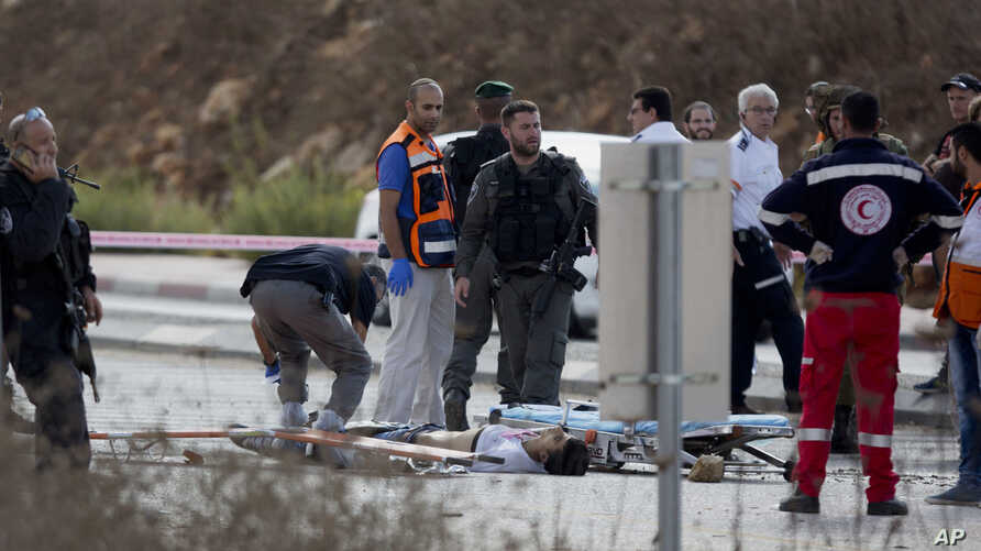 An Israeli forensic officer inspects the body of a Palestinian man at a checkpoint near the West Bank town of Nablus, Oct. 30, 2015. Israeli police said two Palestinians ran toward the checkpoint with knives in their hands, drawing Israeli fire that ...