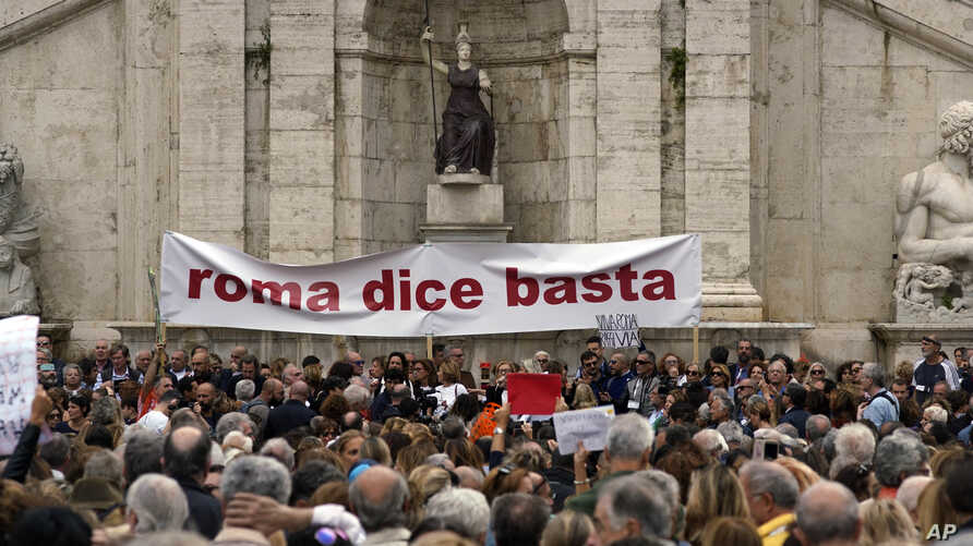 """Rome residents, fed up with what they say is the ongoing decay of the city, rally in front of the city's Campidoglio Capitol Hill, Oct. 27, 2018. The banner reads """"Rome Says Enough."""""""