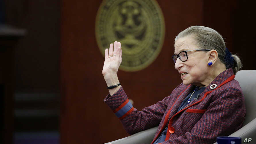 """Supreme Court Justice Ruth Bader Ginsburg waves goodbye to those who came to listen and participate in her """"fireside chat"""" in the Bruce M. Selya Appellate Courtroom at the Roger William University Law School in Bristol, Rhode Island, Jan. 30, 2018."""