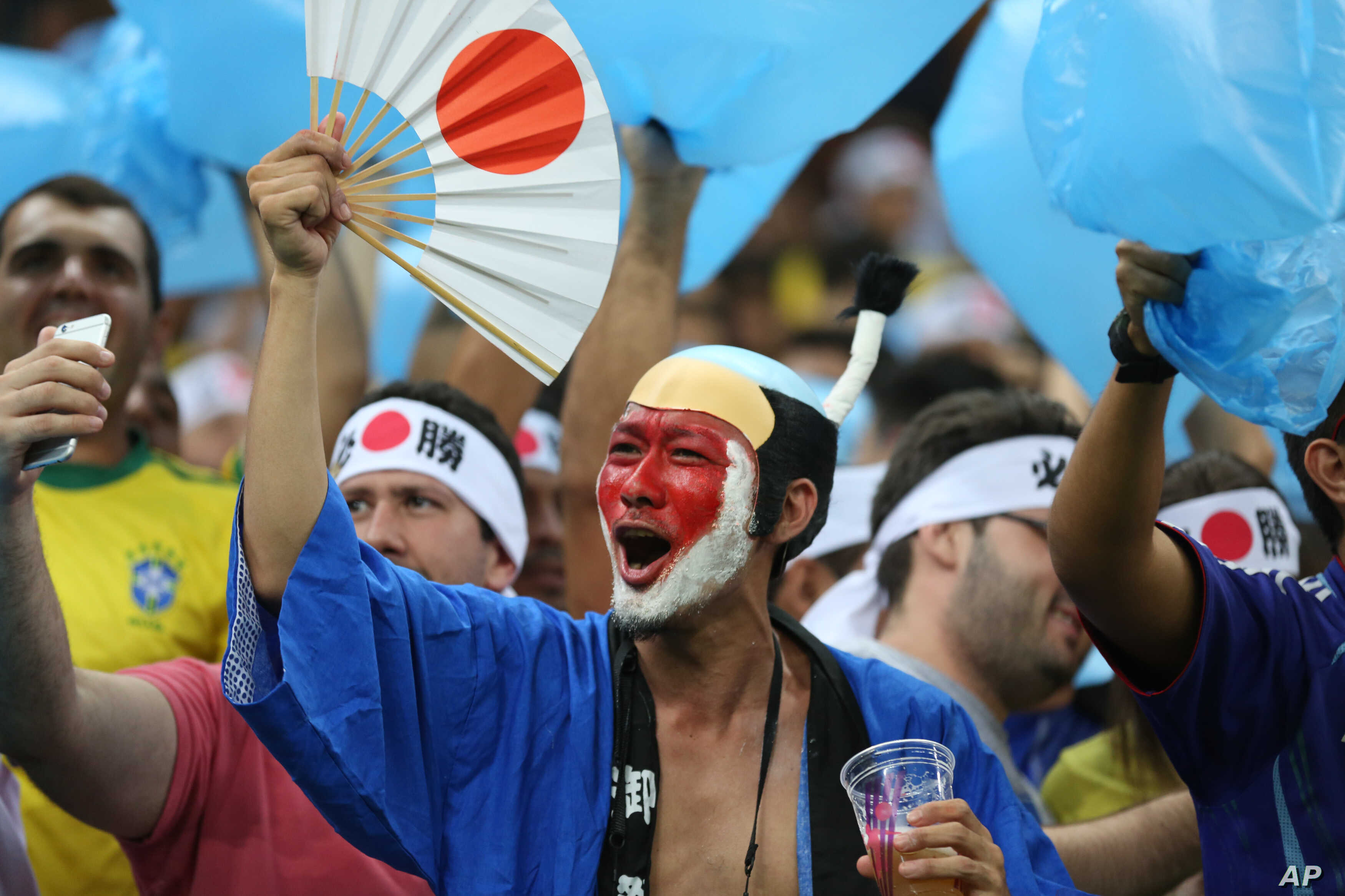 Fans of Japan's Olympic football team cheer for their team during a group B match of the men's Olympic football tournament between Japan and Nigeria at the Amazonia Arena, in Manaus, Brazil, Aug. 4, 2016.