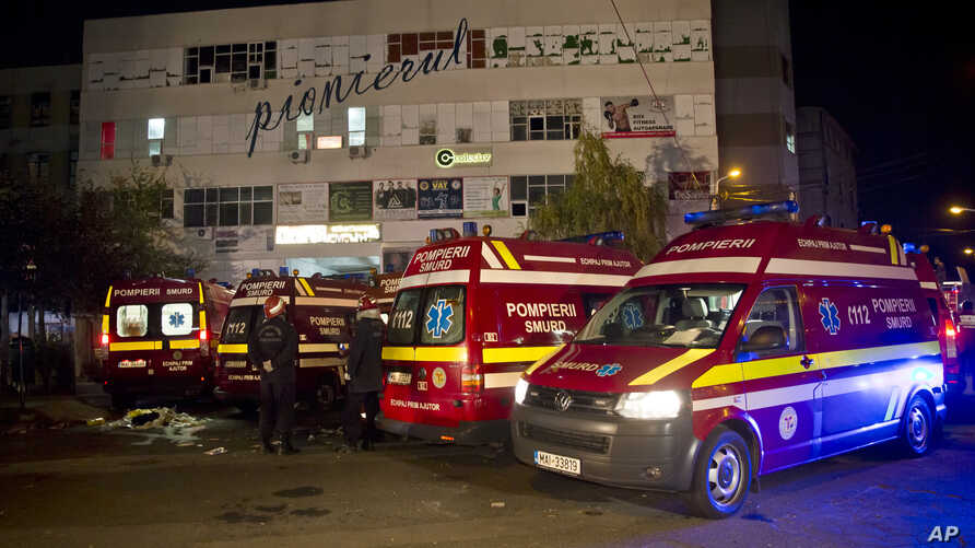 Ambulances are parked outside the site of an explosion that occurred in a club, housed by the building in the background, in Bucharest, Romania, early Saturday, Oct. 31, 2015.