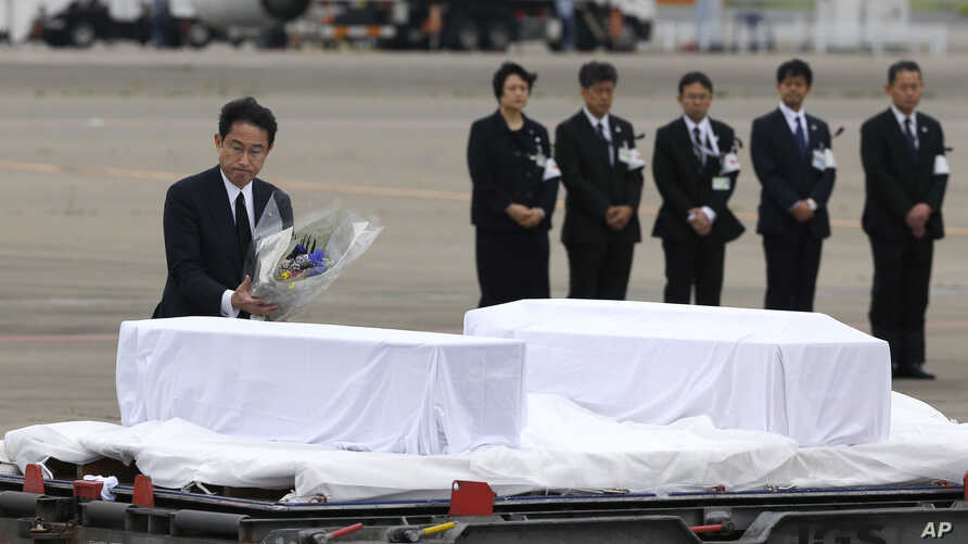 Japanese Foreign Minister Fumio Kishida, left, lays flowers on the coffins of the victims who were killed in the last weekend's attack on a restaurant in Bangladeshi capital Dhaka, at Haneda Airport in Tokyo, Tuesday, July 5, 2016.