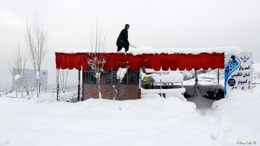 An Afghan man removes snow from his shop on the outskirts of Kabul, Feb. 5, 2017.
