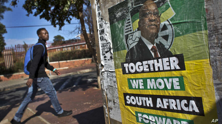 A man walks past an election poster of Jacob Zuma's African National Congress (ANC) party in the Soweto township of Johannesburg, South Africa Friday, May 9, 2014. Vote-counting in elections in South Africa is almost complete, indicating a comfortabl
