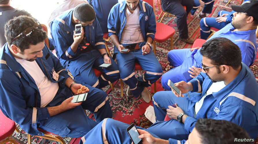 Kuwait Oil and Petrochemical Industries Union workers sit with their cellphones on the first day of an official strike over public sector pay reforms, in Ahmadi, Kuwait, April 17, 2016.