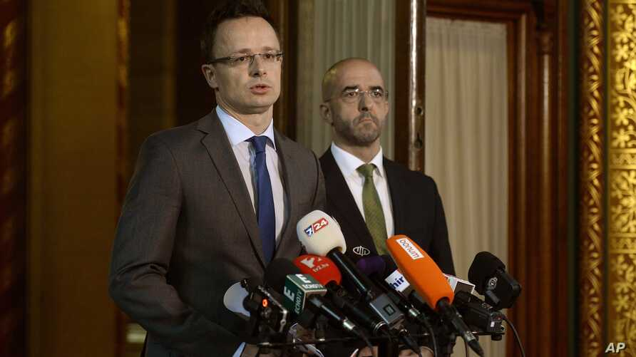 Hungarian Foreign Minister Peter Szijjarto, with government spokesman Zoltan Kovacs at right, talks during a news conference in the parliament building in Budapest about his country's plans to build a fence along the Hungarian-Serbian border to try t