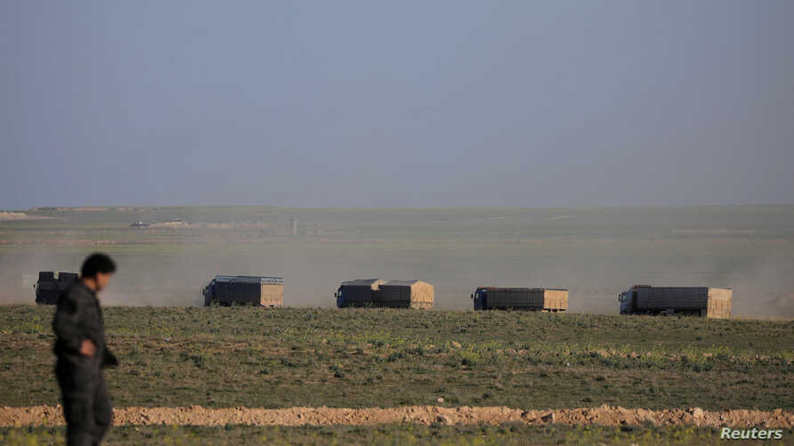 Trucks move near Baghouz, Deir Al Zor province, Syria, February 19, 2019.