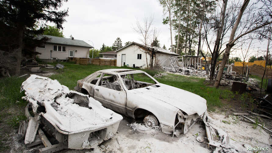 A burnt automobile and boat are seen as thousands of evacuees who fled a massive wildfire begin to return to their homes in Fort McMurray, Alberta, Canada, June 1, 2016.