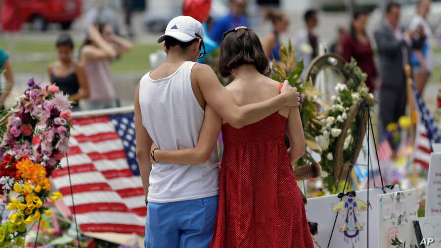 A couple spend a quiet moment at a makeshift memorial honoring the victims of the Pulse nightclub mass shooting, June 20, 2016, in Orlando, Fla.