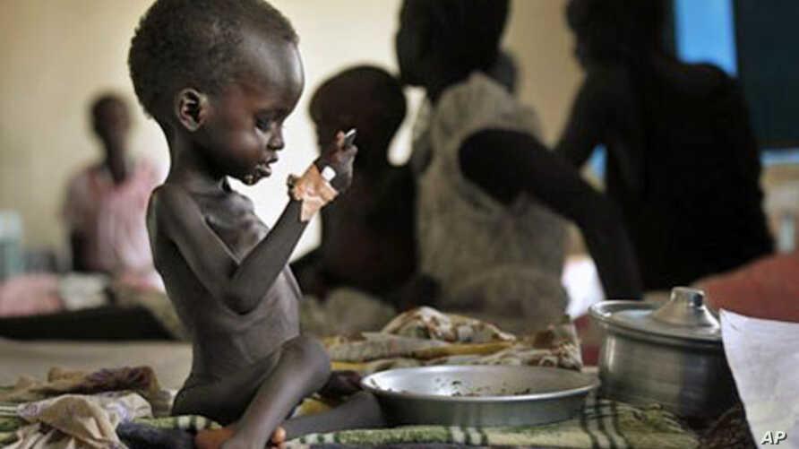 """Two-year-old Nyagod Kuel attempts to eat on her bed in a hospital ward in Akobo, southeastern Sudan. The U.N. mission dubs the """"hungriest place on earth"""". (File)"""