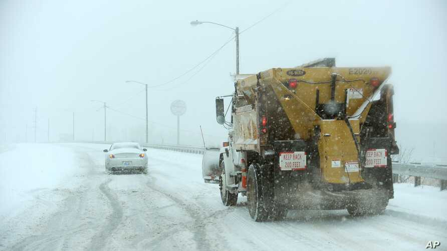 Driver struggles to climb overpass on Hinkleville Road as a snow plow approaches, Paducah, Kentucky, Dec. 6, 2013.