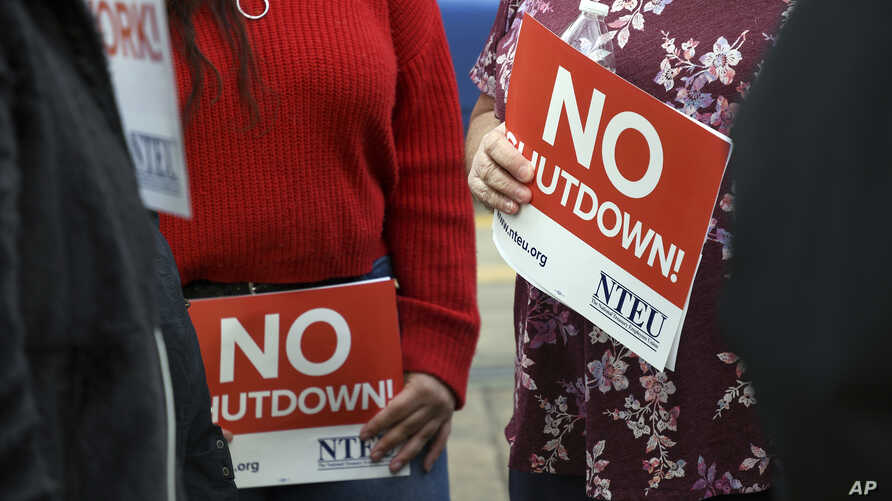 FILE - People protest the partial government shutdown in downtown Denver, Colorado, Jan. 10, 2019. Some federal workers are taking second jobs to stay afloat.