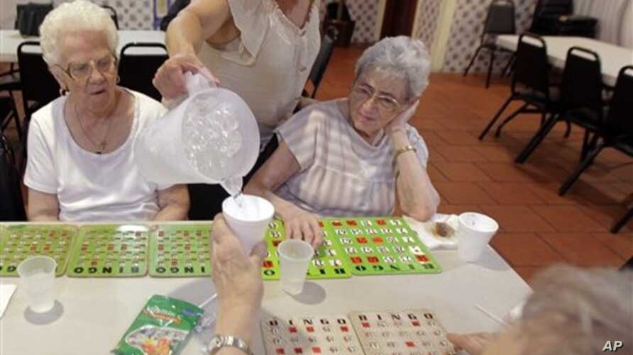 Cristina Couto, supervisor at Ironbound Senior Center, pours water for Jenny Zeama, 84, bottom, as a group of elderly people play bingo, Newark, New Jersey, June 21, 2012.