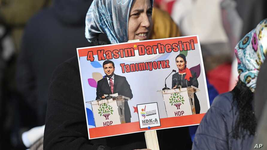 FILE - A protestor shows pictures of detained Turkish HDP politicians Selahattin Demirtas and Figen Yuksekdag at a demonstration  against Turkish president Recep Tayyip Erdogan and the political repression that followed July's failed military coup, i