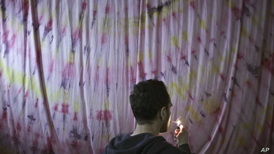 FILE - A gay Egyptian lights his cigarette in Cairo, Egypt. Egypt's gay community is going deeper underground in fear after police arrest dozens of men at a Cairo bathhouse in a raid that was then featured on a lurid TV tabloid program stirring up pu
