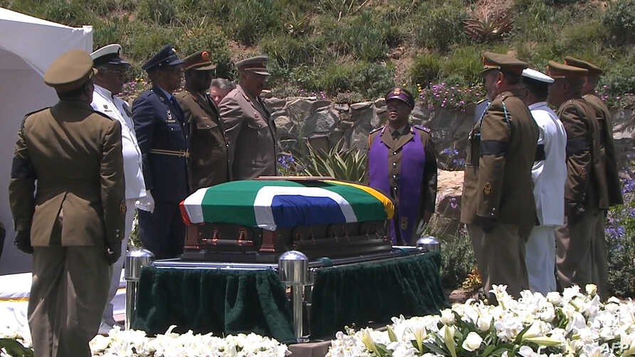 A screengrab taken from the South African Broadcasting Corporation live feed shows members of the South African armed forces standing around the coffin of late former President Nelson Mandela before it is lowered into the grave during his funeral in