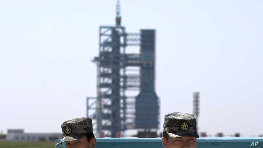 FILE - Chinese soldiers stand guard near the assembly of the Long March 2F rocket and the Shenzhou 10 spacecraft at the Jiuquan Satellite Launch Center in Jiuquan in northwest China's Gansu Province .