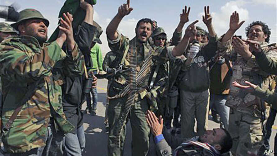 Libyan rebels celebrate as they hear about air strikes at front line near Brega, Libya, April 1, 2011