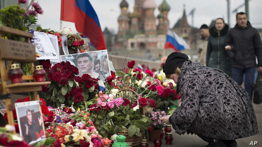 A woman lights a votive candle at the location where Russian opposition politician and Putin foe Boris Nemtsov was gunned down on February 27, 2015, near the Kremlin, in Moscow, Russia, April 7, 2015.