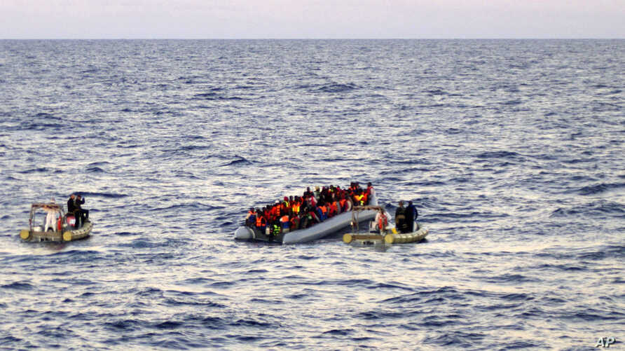 Photo provided by the Italian Navy shows rescue crews approaching migrants on a rubber boat some 40 miles (65 kilometers) from the Libyan capital, Tripoli.