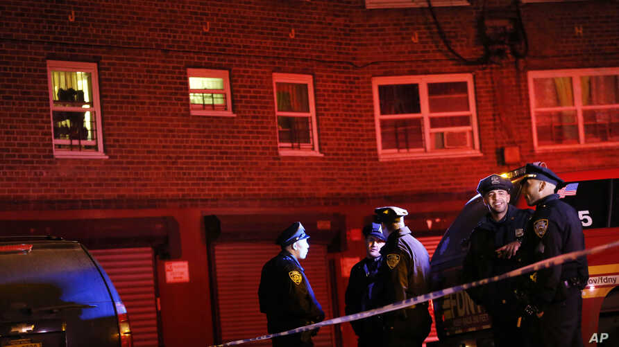 FILE - Emergency officials gather near the site where two police officers were shot in the Bronx section of New York.