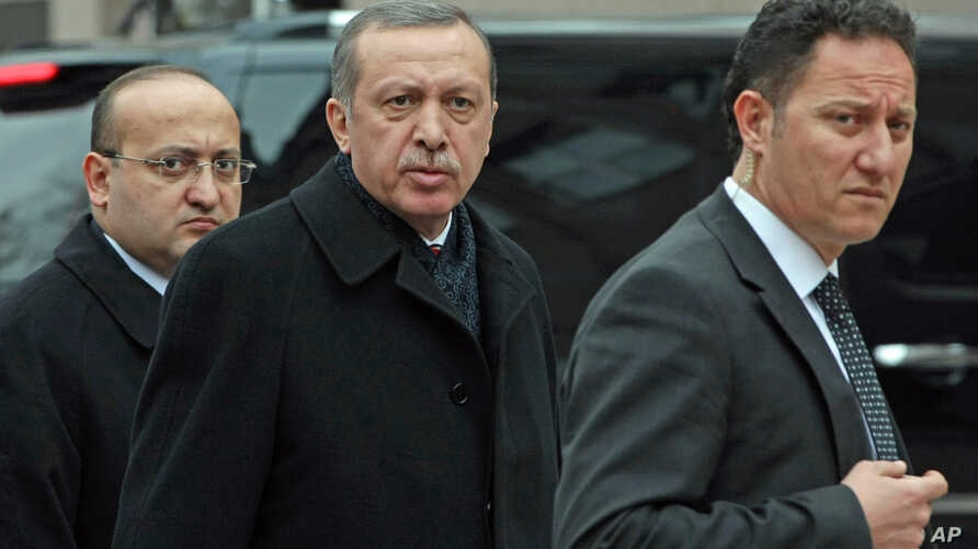 Turkish Prime Minister Recep Tayyip Erdogan, center, is flanked by his advisor Yalcin Akdogan, left, and a security official as he arrives in his office in Ankara, January 30, 2013.