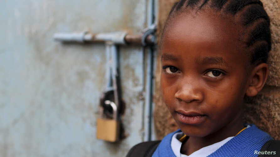 A girl stands next to her locked classroom as a nationwide strike by Kenyan teachers demanding a salary increase left most learning institution paralyzed, in Nairobi, September 5, 2012.