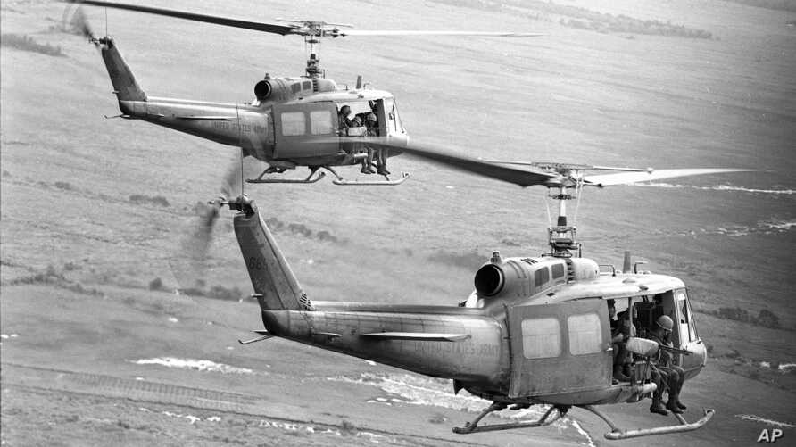 FILE - Soldiers of the U.S. 25th Infantry Division dangle their feet over the sides as they are transported by helicopter into an operational area in the Mekong Delta southwest of Saigon, Aug. 9, 1967.  The unit was on a search and clear operation.