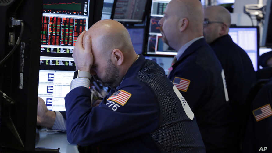 Trader Fred DeMarco, left, works with colleagues in a booth on the floor of the New York Stock Exchange, March 22, 2018.