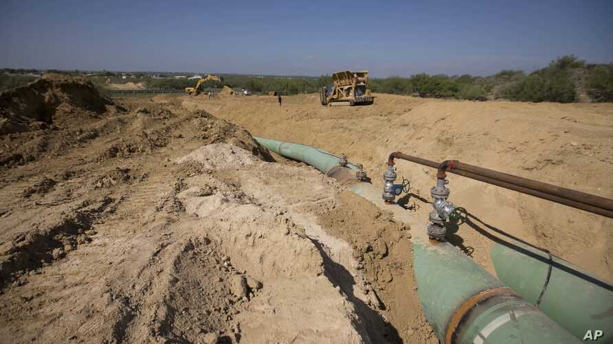 FILE - In this Sept. 7, 2014 photo, new pipelines to carry gas from Texas to Mexico, eventually reaching the city of Guanajuato, are laid underground near General Bravo, in Nuevo Leon state, Mexico.
