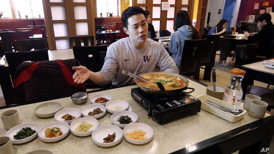 """FILE - Server Young Kim talks about the South Korean dish called budae jjigae, or """"army stew,"""" he is serving simmering atop a heating plate at a Korean restaurant in Shoreline, Washington, Dec. 12, 2017."""