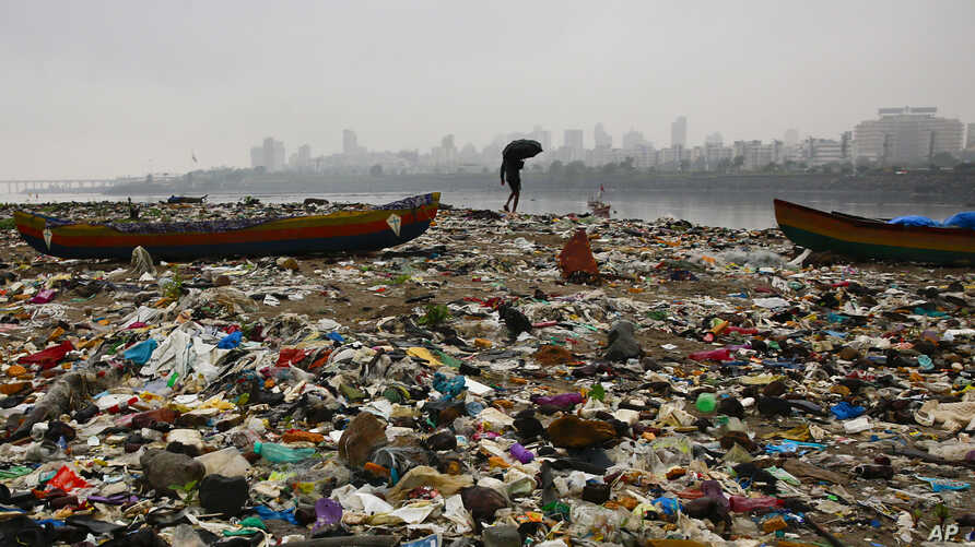 A fisherman walks on the shores of the Arabian Sea, littered with plastic bags and other garbage, in Mumbai, India, Oct. 2, 2016.