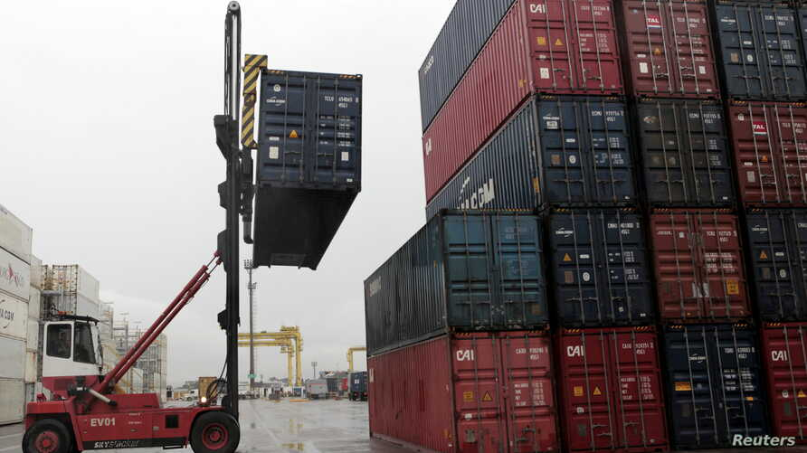 FILE - Workers load containers onto trucks from a cargo ship at a port in Jaragua do Sul, Santa Catarina state, Brazil, Oct. 22, 2015.