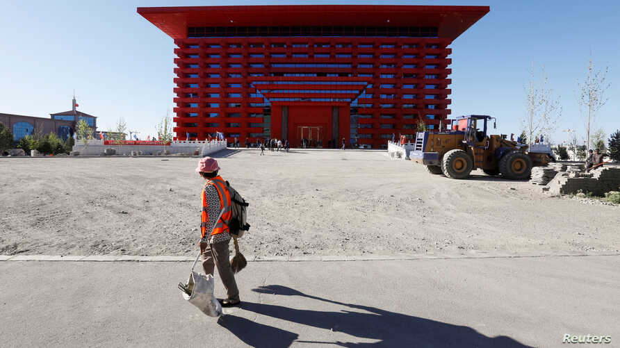 A cleaning worker walks in front of a House of Culture at the Chinese part of the China-Kazakhstan Horgos International Border Cooperation Center (ICBC), in Horgos, China, May 12, 2017.