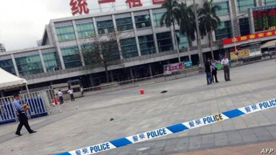 Investigators are seen on the square of Guangzhou railway station after a knife attack in Guangzhou, in southern China's Guangdong province, May 6, 2014.