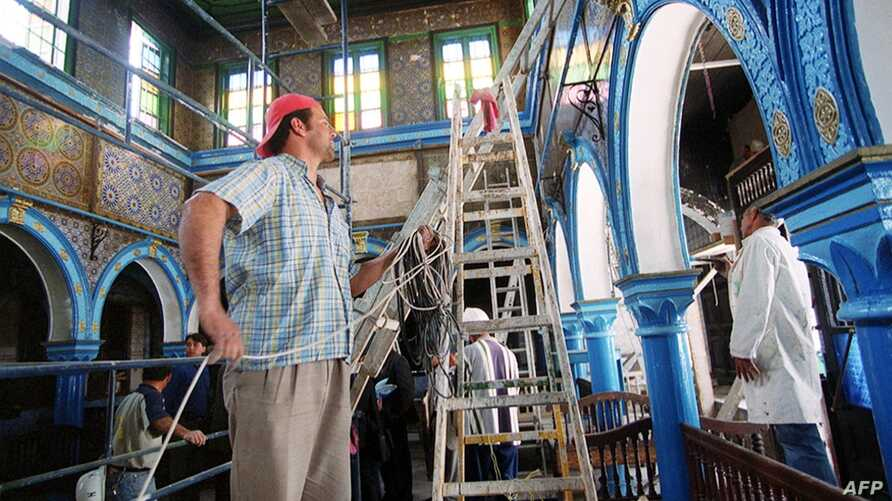 Workers repair damage in the historic Ghriba synagogue in Djerba, April 21, 2002, after an explosion April 11, 2002, causes by a suspected extremist attack that killed 21 people.