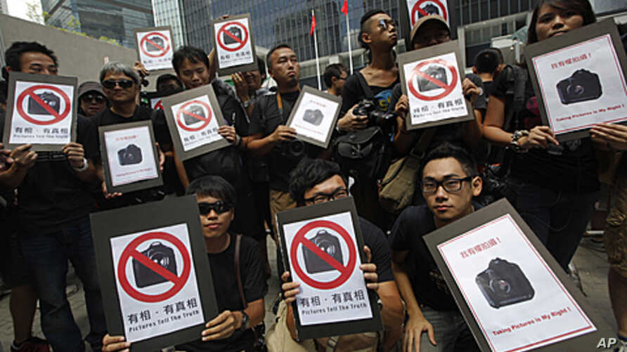 Photo journalists hold placards that read, 'Pictures tell the truth,' during a protest outside the government headquarters in Hong Kong, August 20, 2011 (file photo)