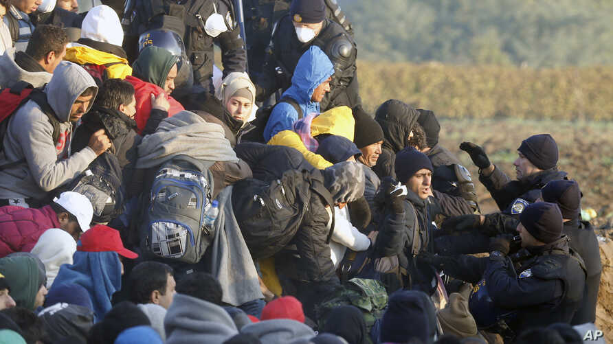 Migrants enter Croatia from Serbia as Croatian police officers stand guard the fence at a border between Serbia and Croatia, near the village of Babska, Croatia, Oct. 21, 2015.