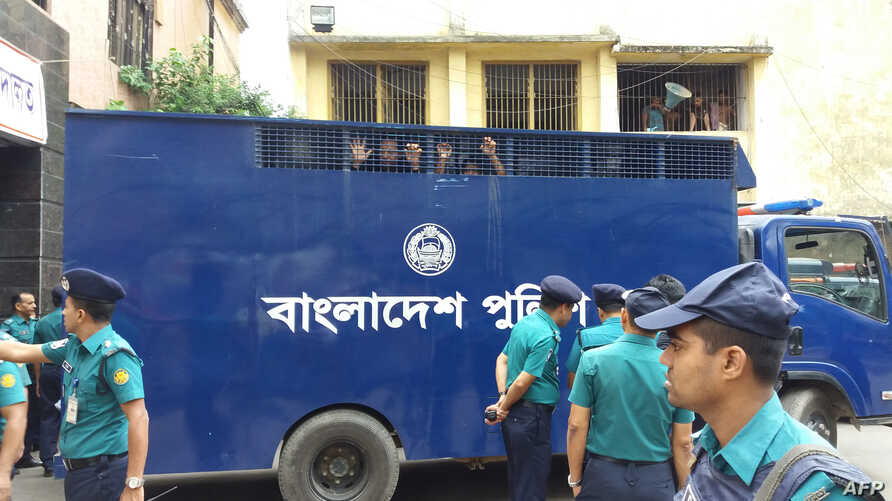 Two co-convicts in a graft case against Bangladesh opposition leader Khaleda Zia in Dhaka look out from a prison van at the premises of a special court in Dhaka on October 29, 2018.