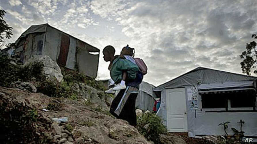 A boy carries a girl to school at a camp for earthquake displaced people in Port-au-Prince, Haiti, Dec 17, 2010