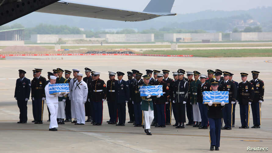 U.N. honor guards carry small boxes containing remains believed to be from American servicemen killed during the 1950-53 Korean War after they arrived from North Korea, at Osan Air Base in Pyeongtaek, South Korea, July 27, 2018.