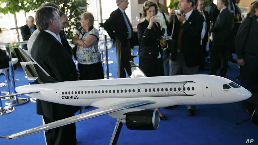 """FILE - People gather around a model of C Series Bombardier airplane on the eve of the Farnborough aerospace show,  Farnborough, England, July 13, 2008. Boeing has accused Bombardier of receiving government subsidies that let it engage in """"predatory p"""
