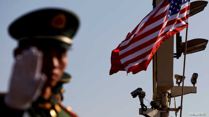 FILE - A paramilitary policeman gestures under a pole with security cameras and U.S. and Chinese flags near the Forbidden City ahead of a visit by U.S. President Donald Trump to Beijing, Nov. 8, 2017.