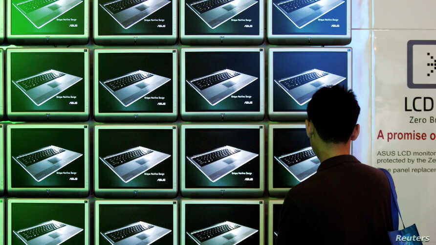 FILE - A visitor looks at ASUS computer screens at the Computex trade show in Taipei.