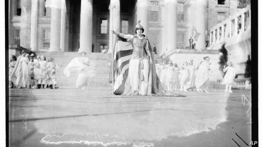 """In this photo provided by the Library of Congress, taken in 1913, German actress Hedwig Reicher wearing costume of """"Columbia"""" with other suffrage pageant participants standing in background in front of the Treasury Building in Washington."""