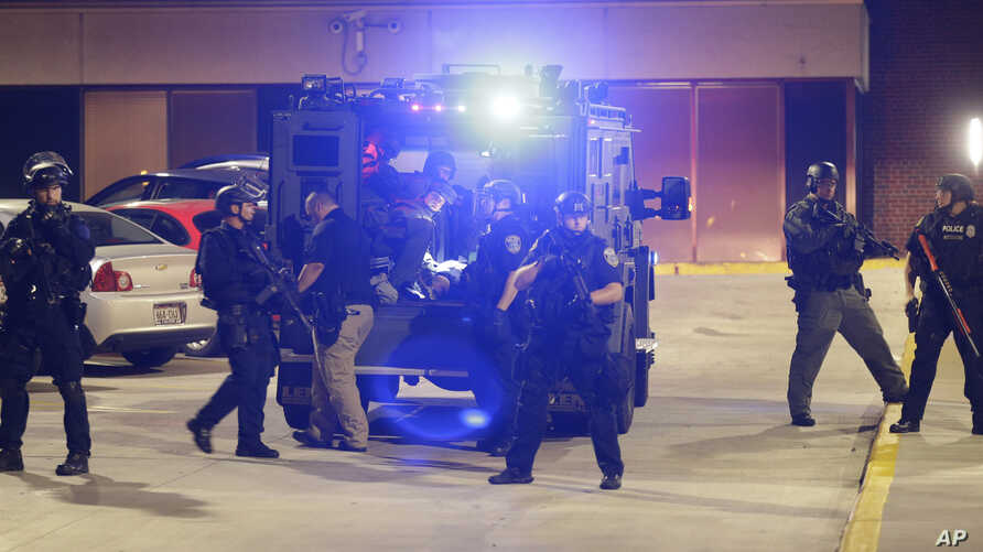 Armed police transport a man to a hospital after getting injured during unrest in Milwaukee, Aug. 14, 2016.