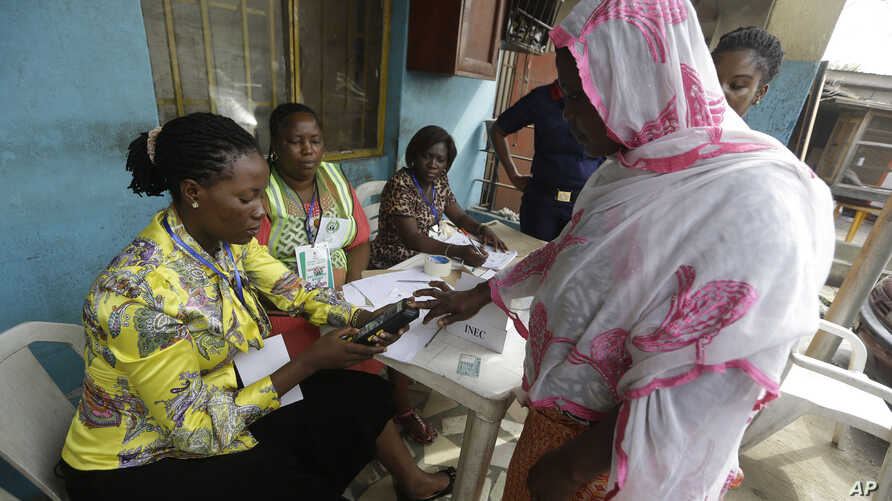 FILE - Semiu Taiwo, right,  gets  her biometric reading taken during an exercise organised by the Independent National Electoral Commission to test run smart card readers.