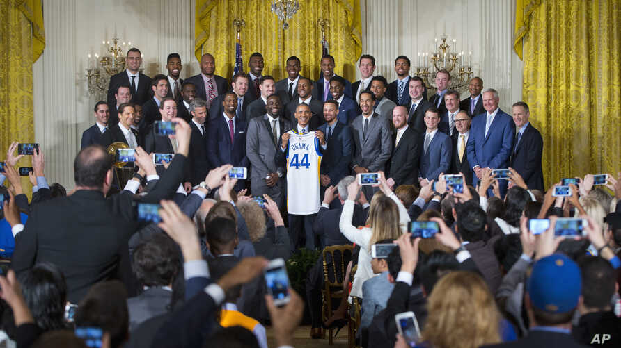 President Barack Obama holds up a Golden State Warrior basketball jersey while posing for a group photo with the team members during a ceremony where he honored the 2015 NBA Champions, in the East Room of the White House in Washington,  Feb. 4, 2016.