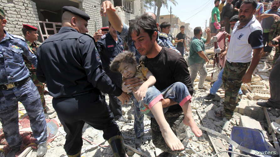 A man carries an injured child found in the rubble after an Iraqi Sukhoi jet accidentally dropped a bomb in Ni'iriya, an eastern district in Baghdad, July 6, 2015..